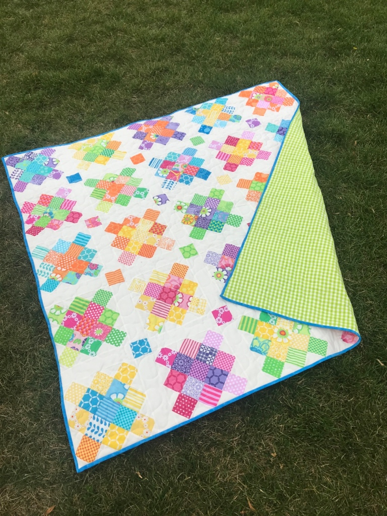Bright, happy Granny Square style quilt laying in the grass.